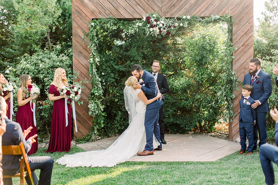 Burgundy-and-Blue-wedding-bride-and-groom-at-ceremony-brdesmaids-in-burgundy-gowns-groomsmen-in-dark-blue-suits-bride-in-a-formfitting-white-lace-gown-with-a-strapless-neckline-the-groom-is-in-a-dark-blue-suit-with-an-ivory-long-tie