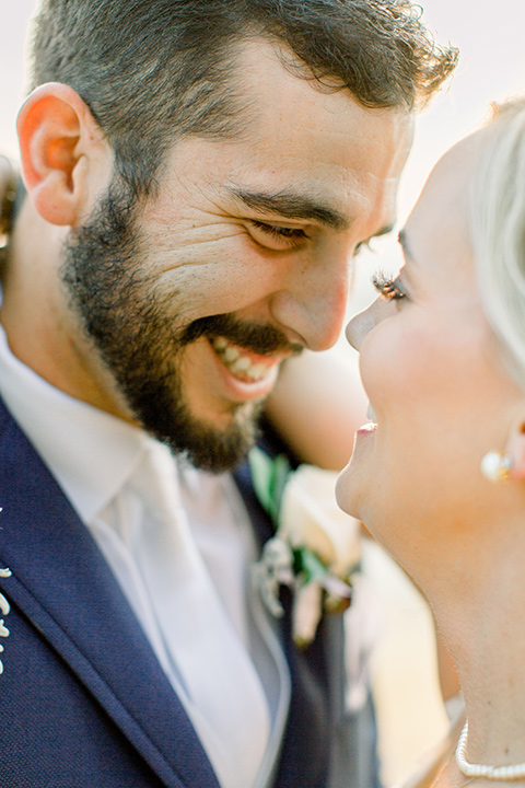 Burgundy-and-Blue-wedding-bride-and-groom-close-up-bride-in-a-white-lace-gown-with-a-sweetheart-neckline-groom-in-a-dark-blue-suit-with-a-white-neck-tie