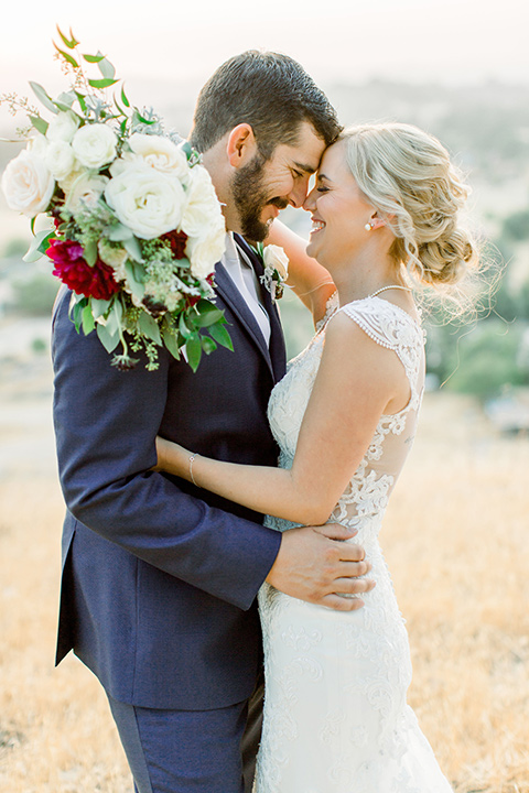 Burgundy-and-Blue-wedding-bride-and-groom-touching-heads-bride-in-a-lace-white-gown-with-a-sweetheart-neckline-groom-in-a-dark-blue-suit-with-a-white-tie