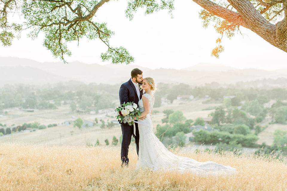 Burgundy-and-Blue-wedding-bride-and-groom-under-tree-bride-in-a-formfitting-white-lace-gown-with-a-strapless-neckline-the-groom-is-in-a-dark-blue-suit-with-an-ivory-long-tie