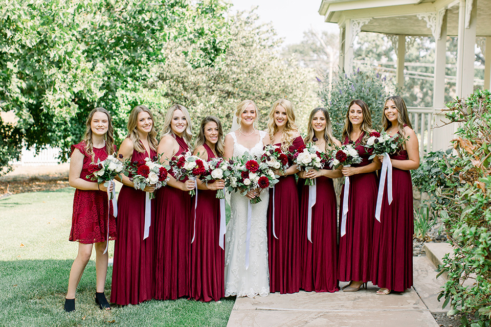 Burgundy-and-Blue-wedding-bridesmaids-dresses-bride-in-a-formfitting-white-lace-gown-with-a-strapless-neckline-bridesmaids-in-deep-burgundy-gowns