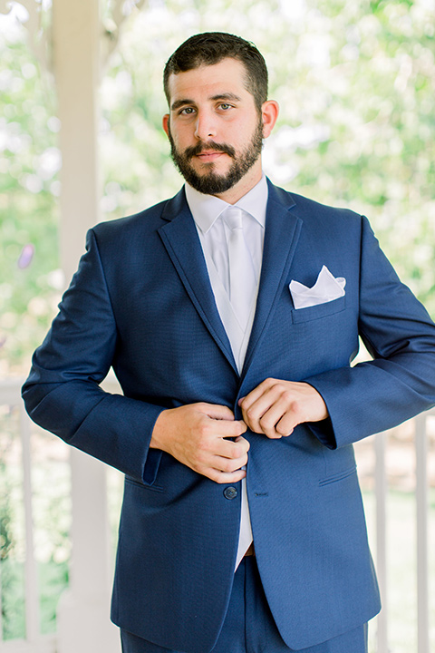 Burgundy-and-Blue-wedding-groom-buttoning-jacket