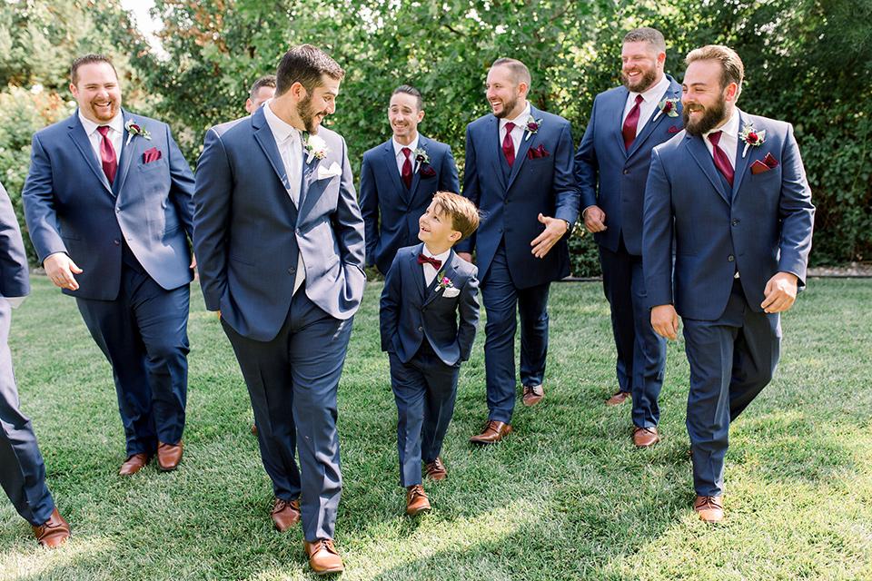 Burgundy-and-Blue-wedding-groomsmen-walking-groomsmen-in-dark-blue-suits-the-groom-is-in-a-dark-blue-suit-with-an-ivory-long-tie
