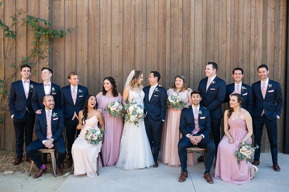 Garden-Wedding-bridalparty-standing-bridesmaids-in-pink-long-dresses-groomsmen-are-in-navy-suits-with-pink-vests-and-pink-bow-ties-bride-in-a-strapless-ballgown-and-groom-in-a-navy-suit-with-a-white-long-tie