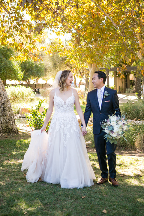 Garden-Wedding-bride-and-groom-walking-bride-in-a-strapless-white-ballgown-and-the-groom-in-a-navy-suit-with-a-white-long-tie-and-pink-pocket-square