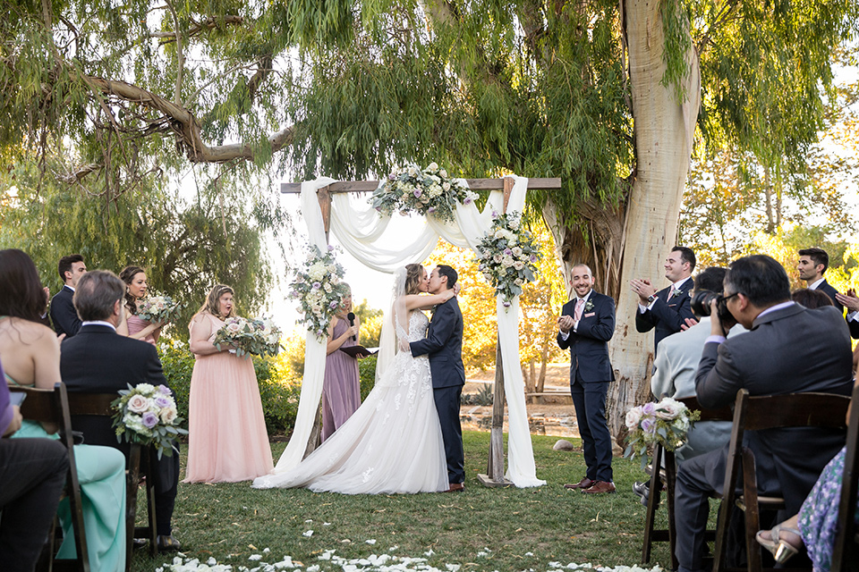 Garden-Wedding-first-kiss-bridesmaids-in-pink-long-dresses-groomsmen-are-in-navy-suits-with-pink-vests-and-pink-bow-ties-bride-in-a-strapless-ballgown-and-groom-in-a-navy-suit-with-a-white-long-tie