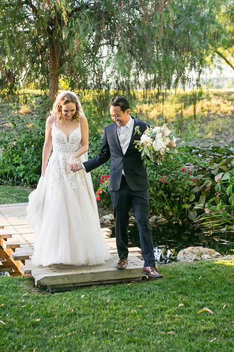 Garden-Wedding-groom-walking-with-bride-bride-in-a-strapless-white-ballgown-and-the-groom-in-a-navy-suit-with-a-white-long-tie-and-pink-pocket-square