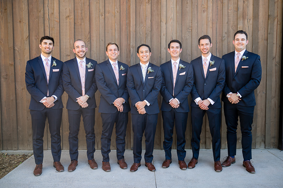 Garden-Wedding-groomsmen-in-a-line-groomsmen-are-in-navy-suits-with-pink-vests-and-pink-bow-ties-and-groom-in-a-navy-suit-with-a-white-long-tie