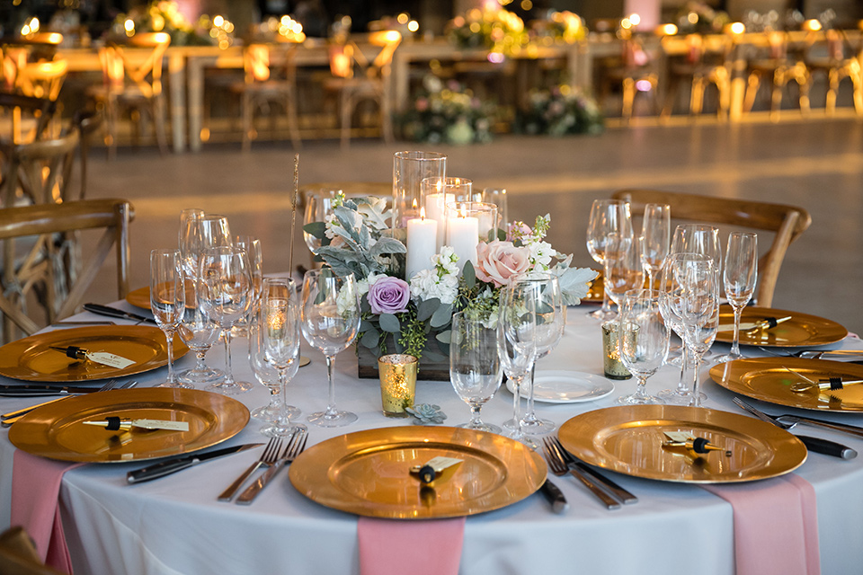 Garden-Wedding-table-decor-drapping-fabrics-and-wooden-table-and-chairs-and-gold-plates-with-pink-napkins