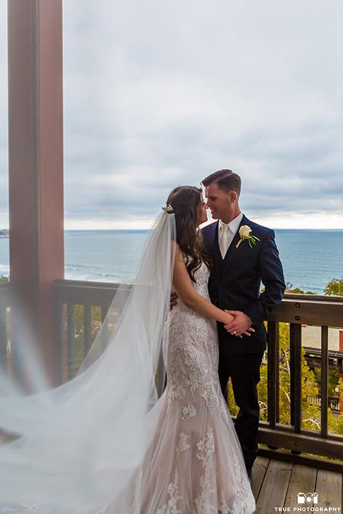 bride and groom pose on a balcony in La Jolla