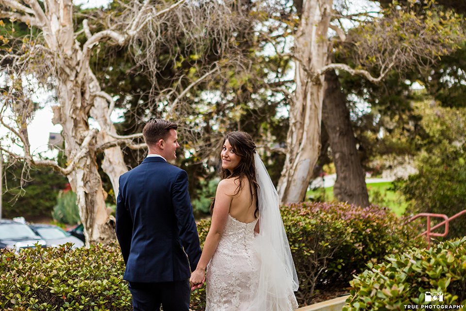 Bride and groom pose for a photo while walking