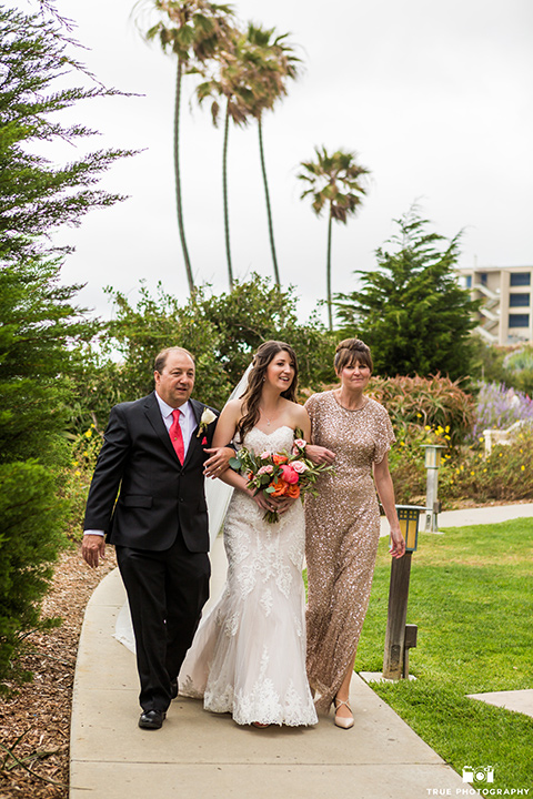 Bride walks down the aisle in a white gown with her parents
