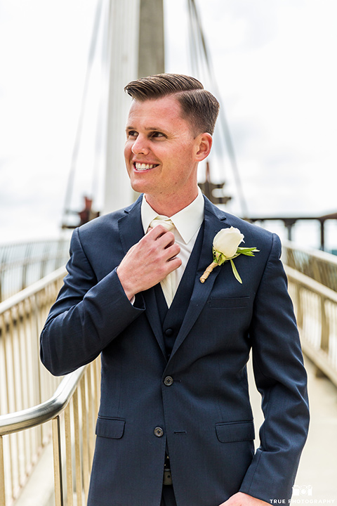Groom fixing white tie in a navy blue suit