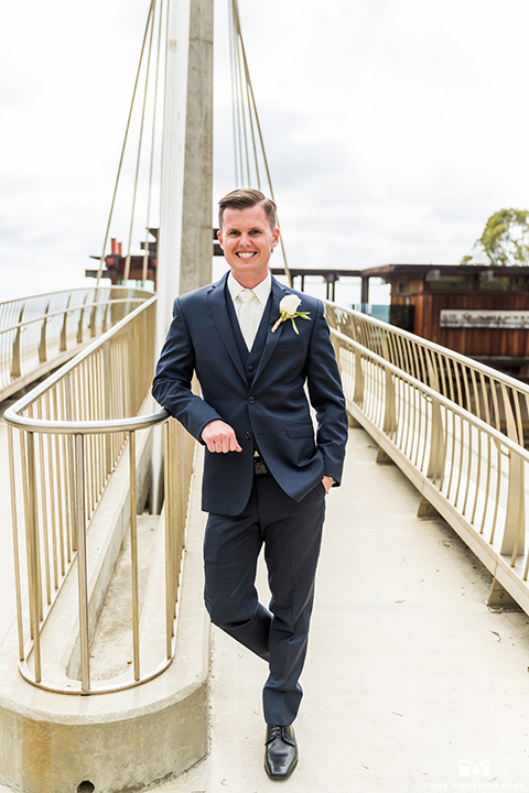 Groom leaning against railing in a navy blue suit and white tie