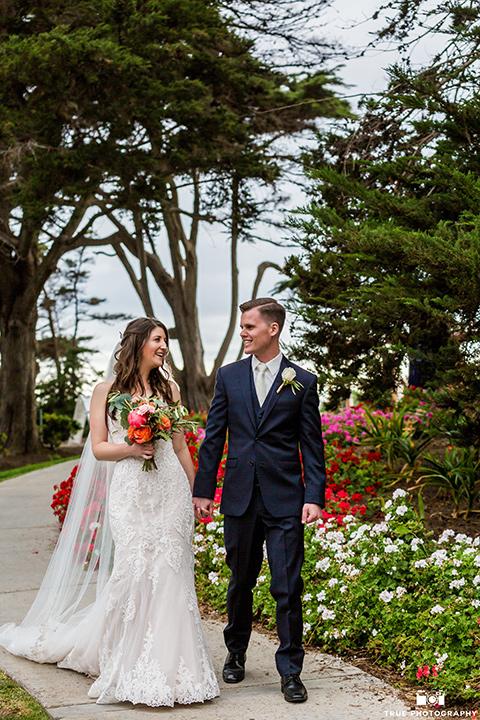 Bride and groom walking towards camera in La Jolla