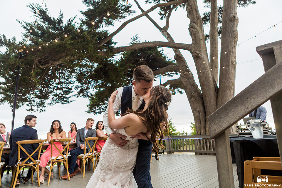 Bride and groom kiss during first dance at wedding