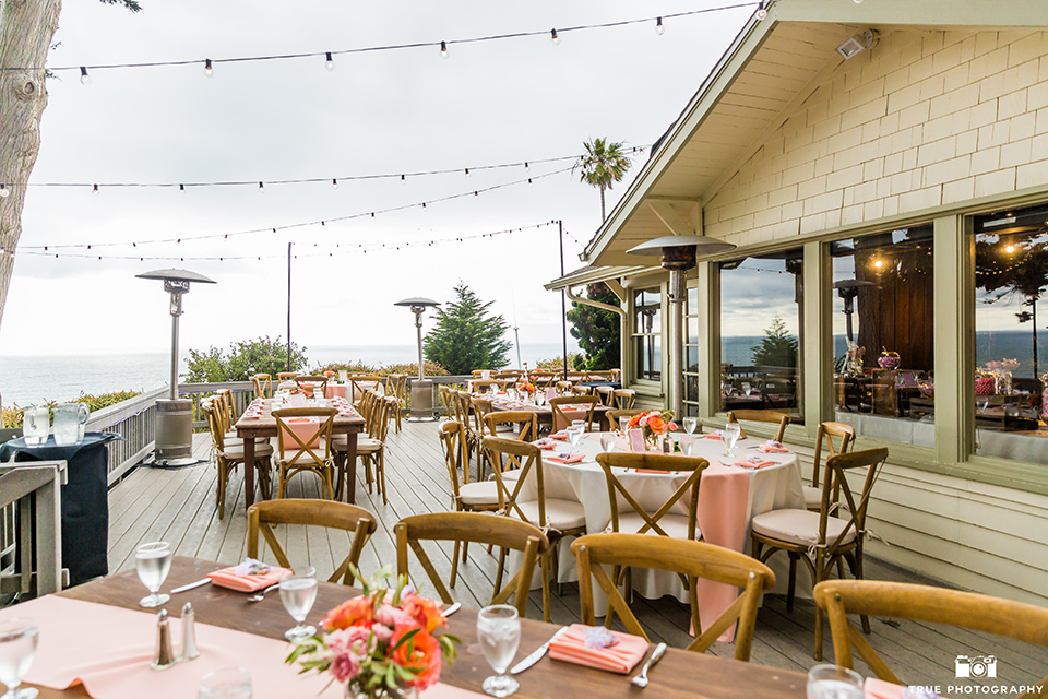 La Jolla wedding reception venue with wooden picnic tables and coral details