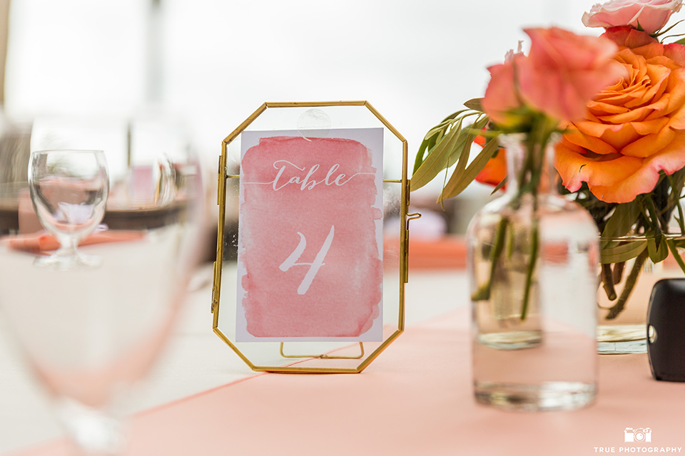 wedding table number cards on wooden picnic tables with coral details