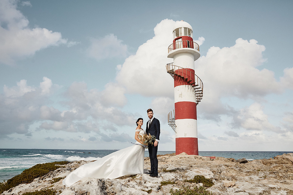 Grand-Firesta-Americana-Coral-Beach-bride-and-groom-by-lighthouse-bride-in-ballgown-groom-innavy-tuxedo