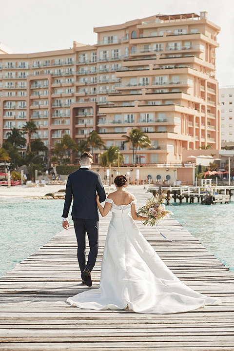 Grand-Firesta-Americana-Coral-Beach-bride-and-groom-walking-away-on-dock