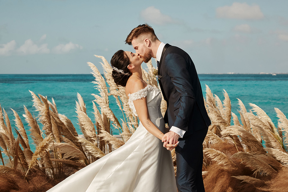 Grand-Firesta-Americana-Coral-Beach-couple-ceremony-kiss-groom-in-navy