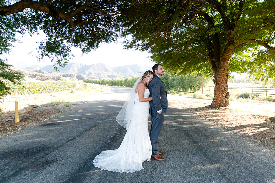 gallaway-downs-wedding-bride-and-groom-in-road-bride-in-a-lace-a-line-gown-and-groom-in-a-navy-blue-suit-with-a-white-long-tie