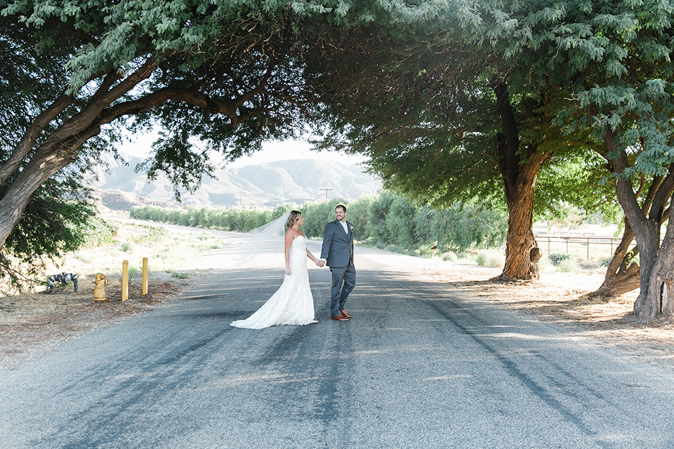 gallaway-downs-wedding-bride-and-groom-walking-across-the-road-bride-in-a-lace-a-line-gown-and-groom-in-a-navy-blue-suit-with-a-white-long-tie