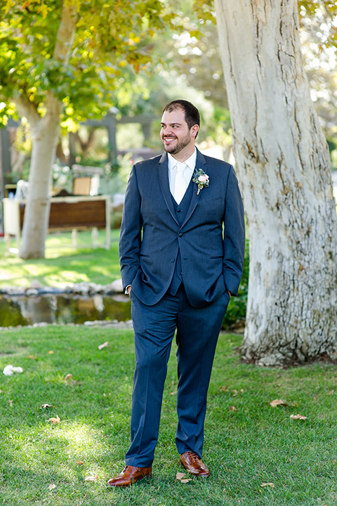 gallaway-downs-wedding-groom-look-to-the-side-in-a-dark-blue-suit-with-a-white-long-tie