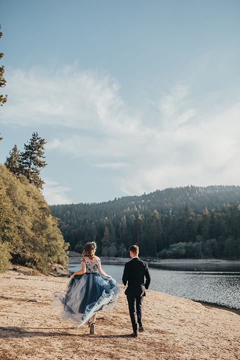 Big-Bear-Elopement-Shoot-bride-and-groom-running-bride-wearing-a-blue-tulle-gown-with-an-illusion-neck-line-and-floral-design-groom-with-black-tuxedo-and-black-bow-tie