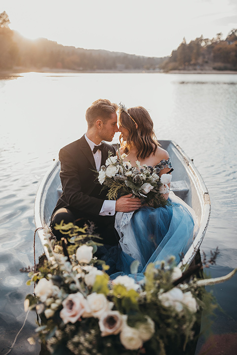 Big-Bear-Elopement-Shoot-bride-and-groom-sitting-in-boat-bride-wearing-a-blue-tulle-gown-with-an-illusion-neck-line-and-floral-design-groom-with-black-tuxedo-and-black-bow-tie