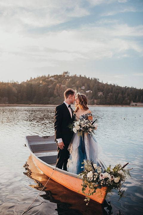 Big-Bear-Elopement-Shoot-bride-and-groom-standing-in-boat-bride-is-in-a-blue-tulle-gown-with-an-illusion-neckline-and-floral-design-the-groom-wore-a-traditional-black-tuxedo-with-a-peak-lapel-and-black-bow-tie