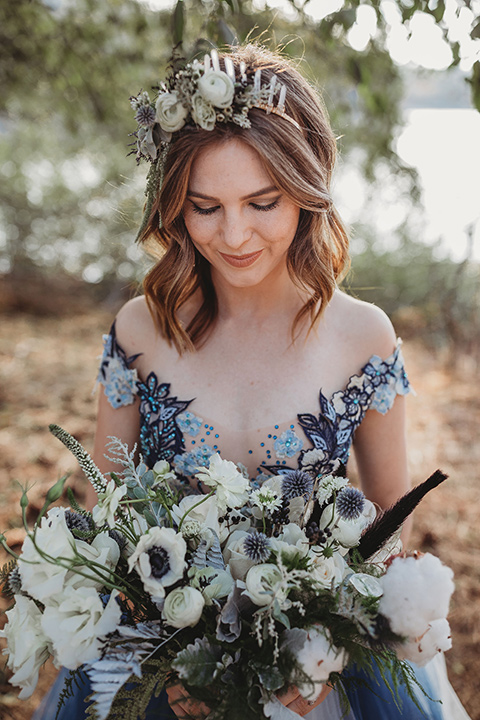 Big-Bear-Elopement-Shoot-bride-holding-flowers-gown-with-an-illusion-neckline-and-floral-design-the-groom-wore-a-traditional-black-tuxedo-with-a-peak-lapel-and-black-bow-tie