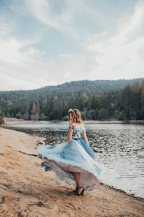 Big-Bear-Elopement-Shoot-bride-spinning-bride-wearing-a-blue-tulle-gown-with-an-illusion-neck-line-and-floral-design-groom-with-black-tuxedo-and-black-bow-tie