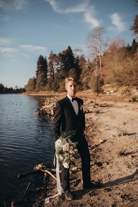 Big-Bear-Elopement-Shoot-groom-holding-flowers-in-a-tuxedo-and-black-bow-tie