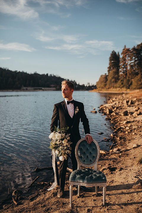 Big-Bear-Elopement-Shoot-groom-standing-by-chair-in-a-traditional-black-tuxedo-with-a-peak-lapel-and-black-bow-tie