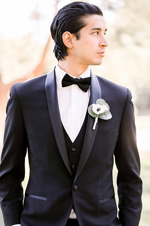 groom in a black shawl lapel tuxedo with a black bow tie