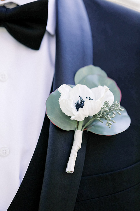 Close up of groom's shawl lapel tuxedo with a Boutonnière