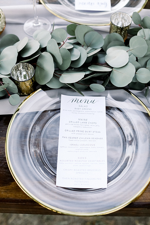 Blomgren Ranch wedding table décor with silver plates and white menu cards