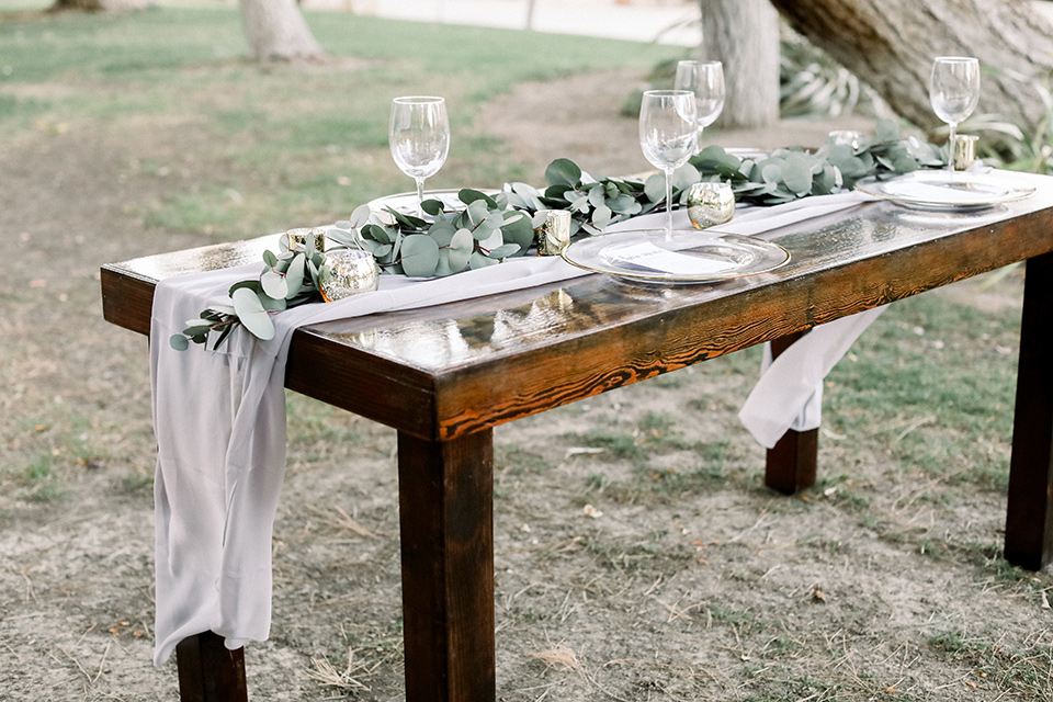 Blomgren Ranch wedding table set up with wood tables in a picnic style with white and green florals and silver flatware