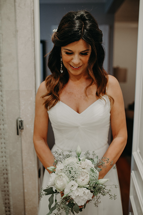 West-Hollywood-Wedding-bride-looking-at-her-flowers-in-a-flowing-white-gown-with-straps