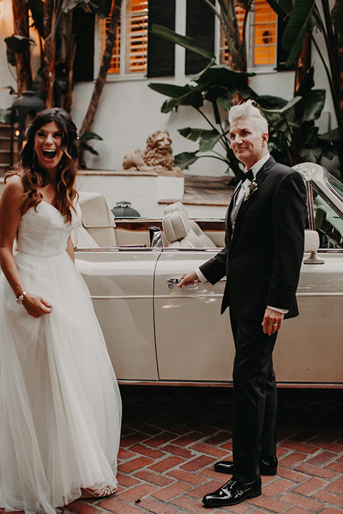 West-Hollywood-Wedding-bride-opening-the-car-door-one-bride-in-a-black-tuxedo-with-a-grey-cvest-and-black-bow-tie-the-other-bride-in-a-flowing-white-gowin-with-a-sweetheasrt-neckline-and-white-straps