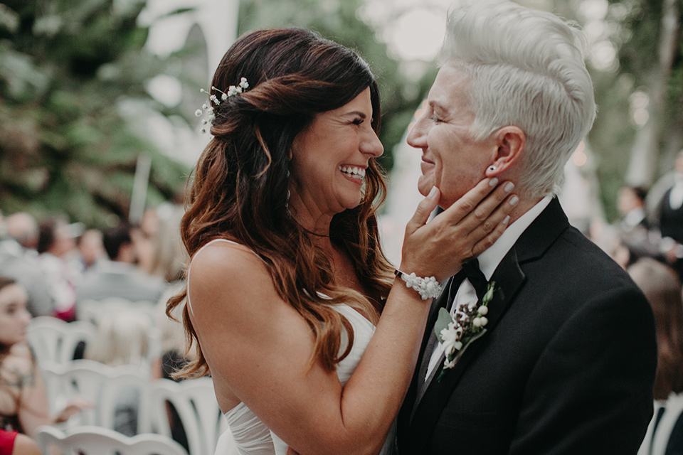 West-Hollywood-Wedding-brides-close-up-one-bride-in-a-black-tuxedo-with-a-grey-vest-and-black-bow-tie-the-other-bride-in-a-flowing-white-gown-with-a-sweetheart-neckline-and-white-straps