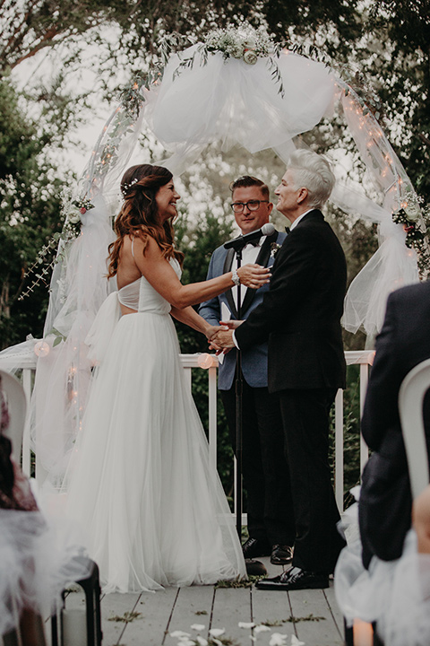 West-Hollywood-Wedding-brides-holding-hands-at-ceremony-one-bride-in-a-black-tuxedo-with-a-grey-cvest-and-black-bow-tie-the-other-bride-in-a-flowing-white-gowin-with-a-sweetheasrt-neckline-and-white-straps