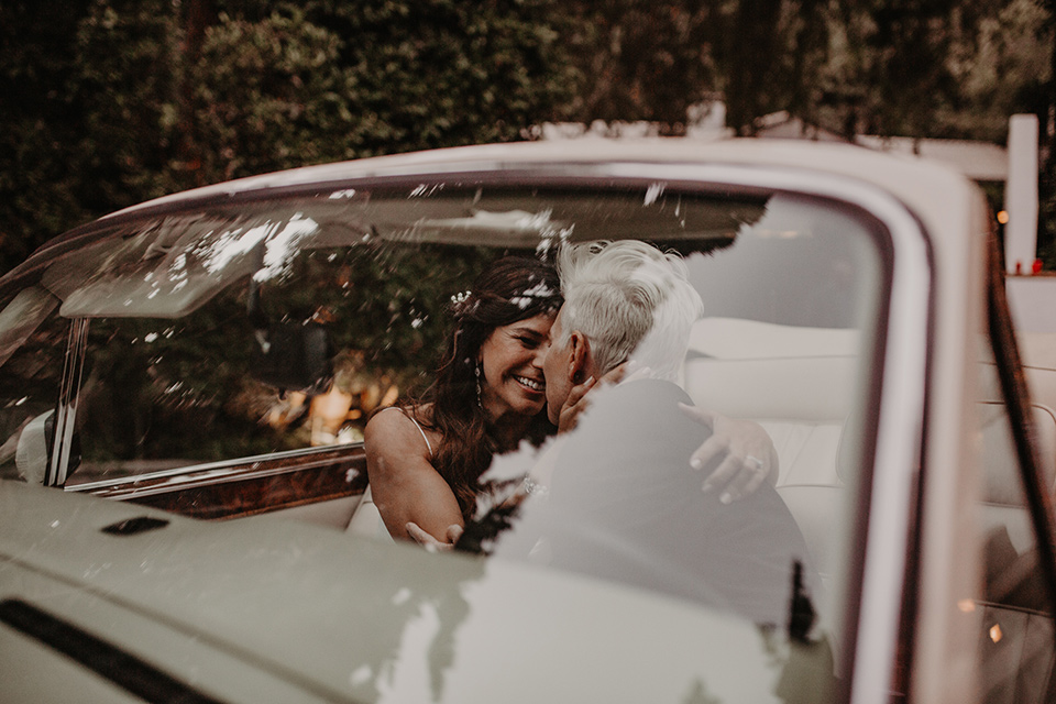 West-Hollywood-Wedding-brides-in-car-one-bride-in-a-black-tuxedo-with-a-grey-vest-and-black-bow-tie-the-other-bride-in-a-flowing-white-gowin-with-a-sweetheasrt-neckline-and-white-straps