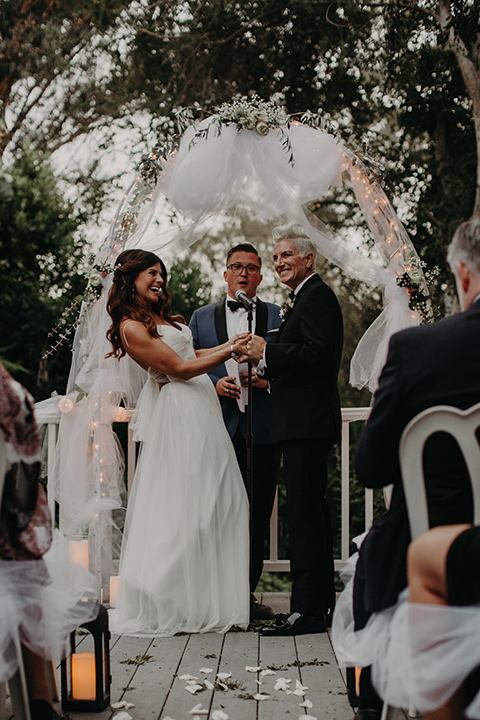 West-Hollywood-Wedding-brides-laughing-at-ceremony-one-bride-in-a-black-tuxedo-with-a-grey-vest-and-black-bow-tie-the-other-bride-in-a-flowing-white-gowin-with-a-sweetheasrt-neckline-and-white-straps