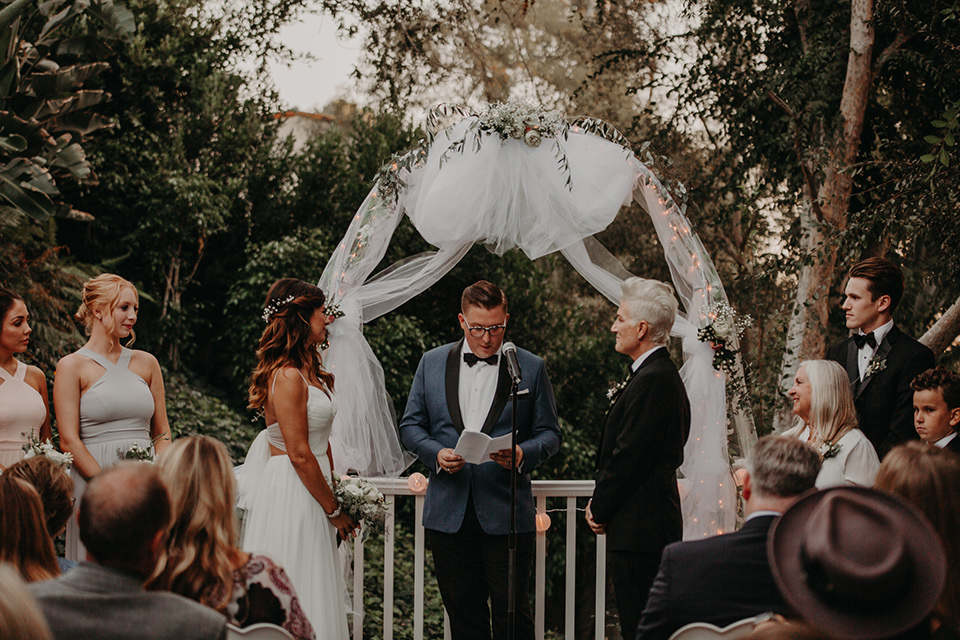 West-Hollywood-Wedding-ceremony-one-bride-in-a-black-tuxedo-with-a-grey-vest-and-black-bow-tie-the-other-bride-in-a-flowing-white-gowin-with-a-sweetheasrt-neckline-and-white-straps