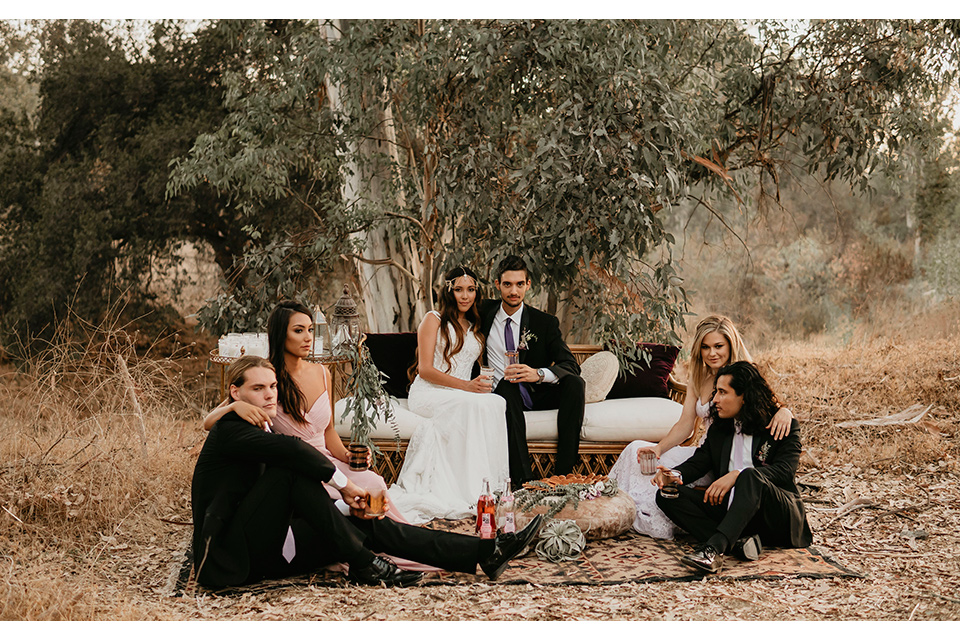 Boho chic elopement wedding with the bridesmaids with soft pink gowns and the groomsmen in black suits the bride in an ivory lace ball gown with a gold chain headpiece and the groom in a black suit with a black long tie and everyone is sitting on the ground with bohemian pillows and carpet
