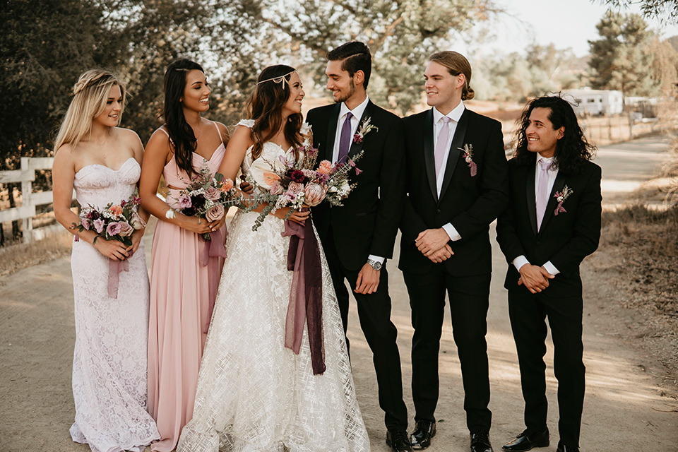 Boho chic elopement wedding with the bridesmaids with soft pink gowns and the groomsmen in black suits the bride in an ivory lace ball gown with a gold chain headpiece and the groom in a black suit with a black long tie