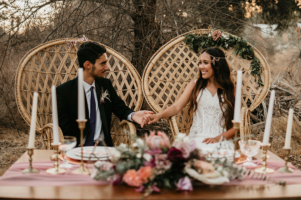 Boho chic elopement wedding with the bride in an ivory lace ball gown with a gold chain headpiece and the groom in a black suit with a black long tie sitting at the sweetheart table in big wicker chairs