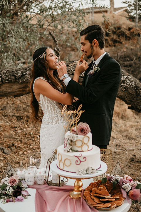 boho elopement shoot with the bride in a lace ball gown and a gold chair headpiece and the groom in a black suit with a long black tie cutting the cake